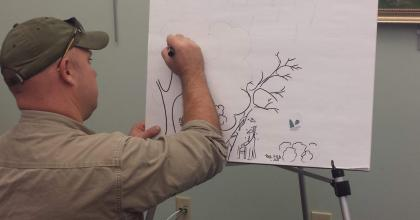 a man drawing a picture of a forest on a flip chart