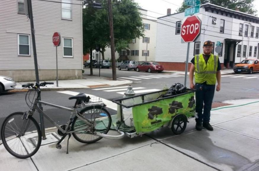 a bicycle with a trailer used for watering with a city worker standing next to it