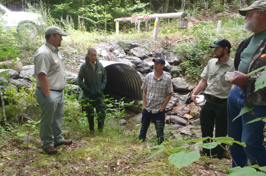 Natural resource professionals standing at the outlet of a large culvert