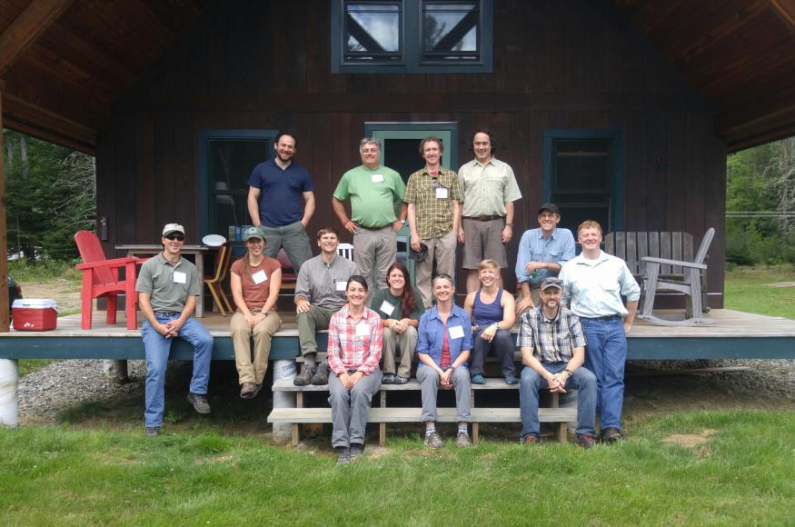Fourteen scientists and managers sit on a porch at the Second College Grant