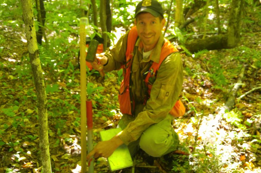 A researcher installs a marker for the center of a research plot.